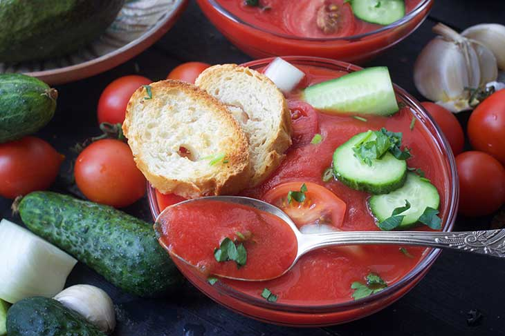 bowl of gazpacho cold soup recipe with fresh raw vegetables on the table