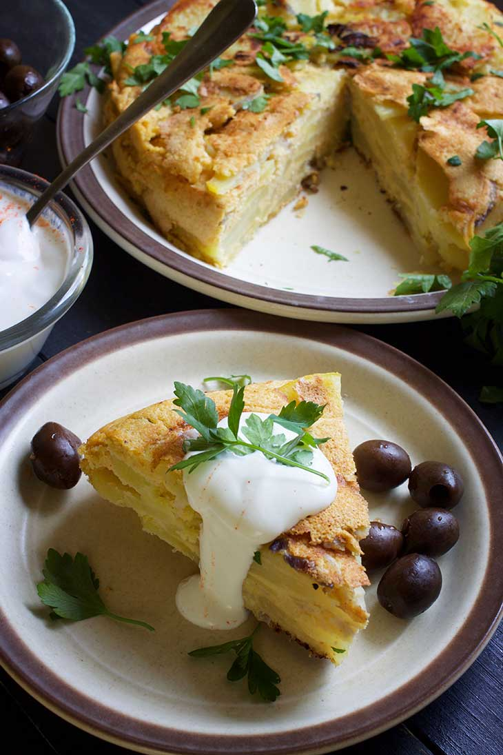 healthy Vegan Potato Tortilla slice served with cream and olives