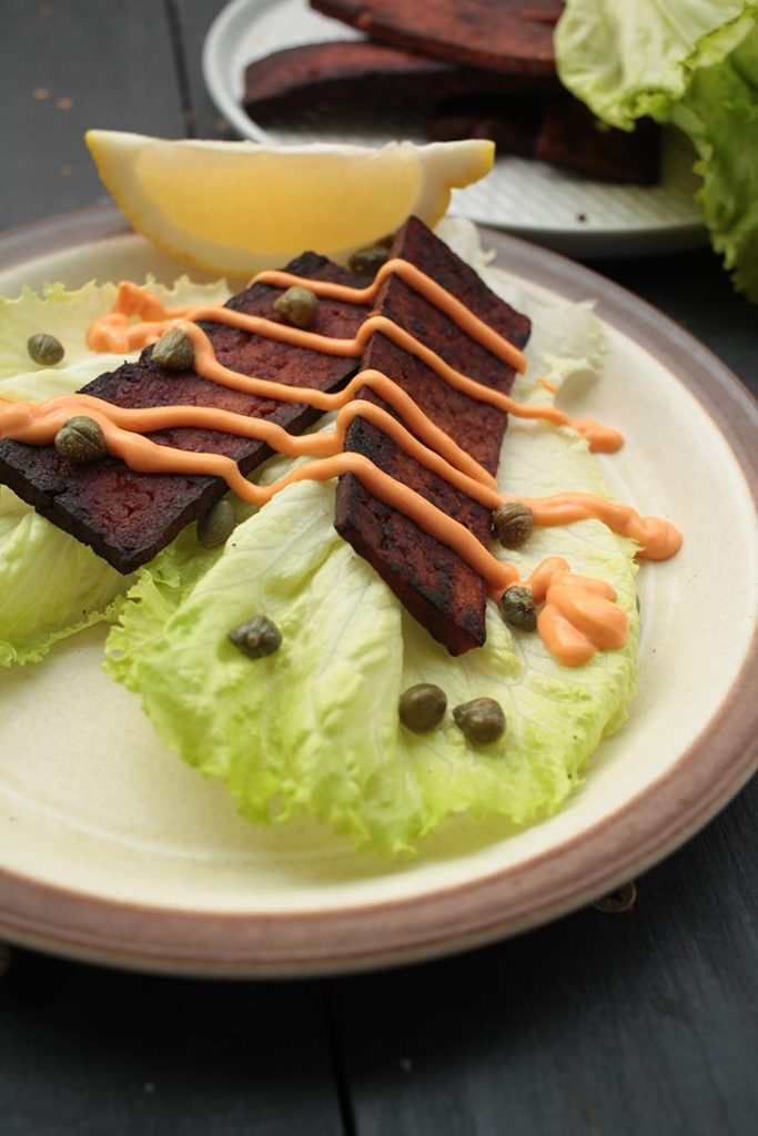 vegan tofu bacon on lettuce with sauce